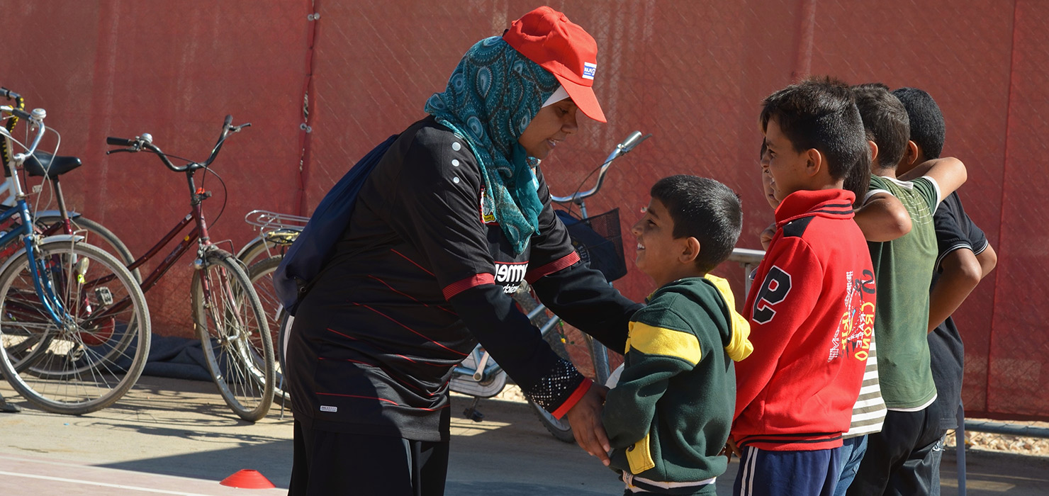 A female Young Coach is instructing ayoung boy